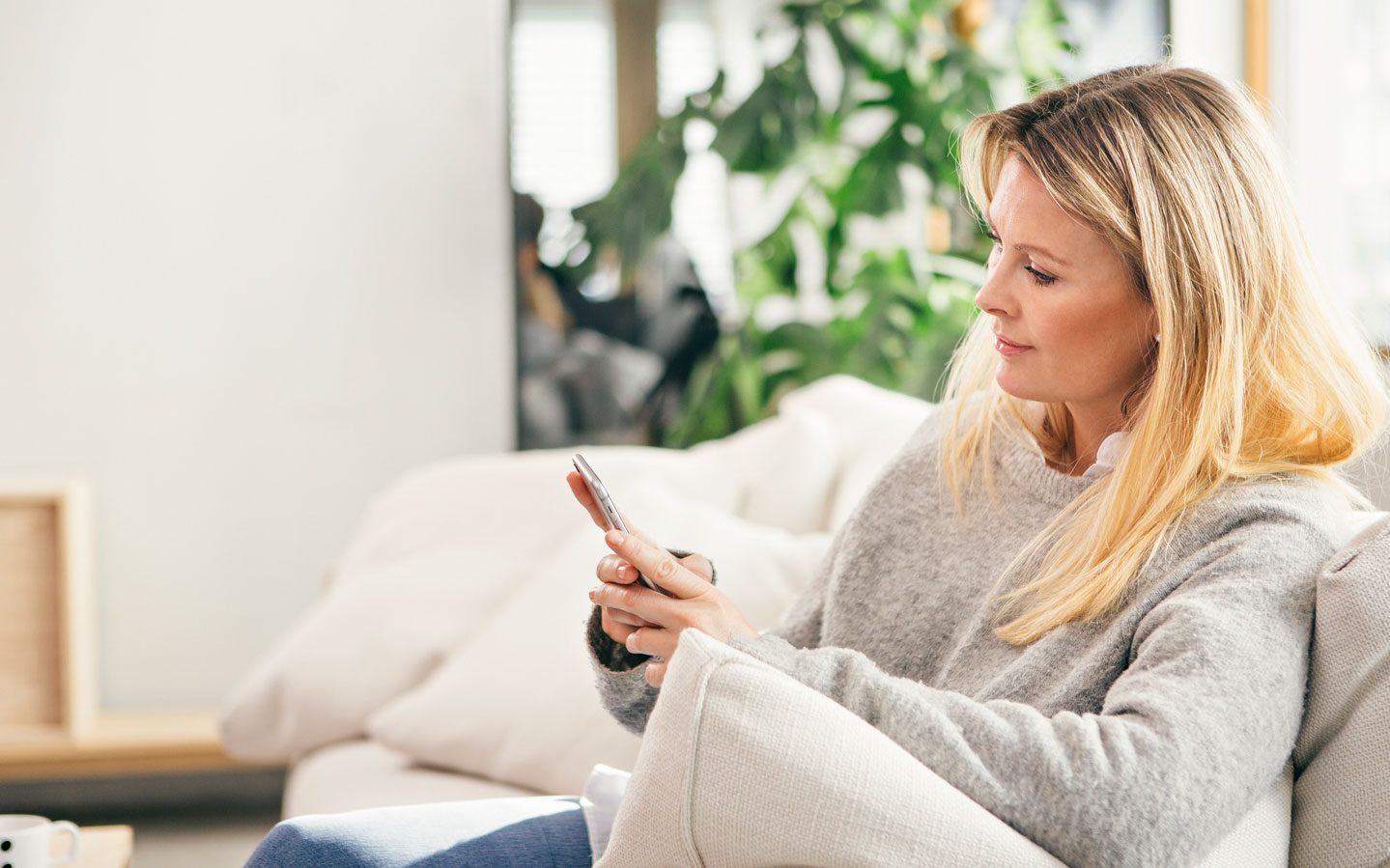 Kvinne leser SMS på mobilen hjemme i sofaen