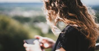 Kvinne som benytter mobilen til å kommunisere med SMS fra Link mobility.