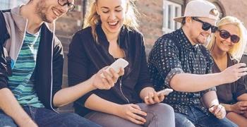 Venner som viser hverandre det de ser på mobilen
