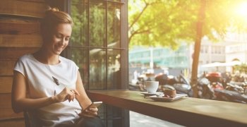 Dame sitter med mobilen på cafè
