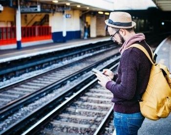 Mann som leser om mobilkommunikasjon og sms på steroiderfør togreise.