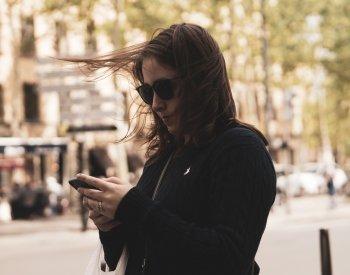 Jente leser melding fra OTT på mobilen